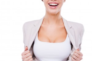 Willing to be the first in business. Close-up of happy young businesswoman taking off her jacket and showing her perfect cleavage while standing against white background